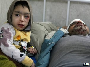 An boy lies next to his injured father at the Imam Ali hospital in Sadr City (24 January 2012)