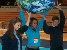 Students hold a model of the world aloft with Team GB athlete Zoe Smith