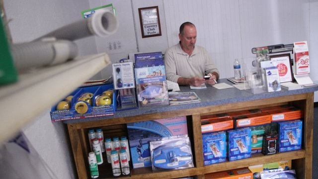 man sits behind counter at pool company