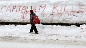 "A girl walks past the slogan ""Capitalism Kills"" written in the snow, Davos"