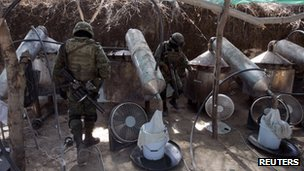 Soldiers stand next to distillers at an outdoor clandestine drug processing laboratory discovered in Tlajomulco de Zuniga, on the outskirts of Guadalajara 23 January 2012.