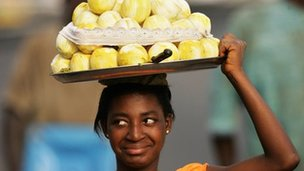 A smiling Ghanaian vendor carrying fruit on her head