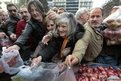 Greeks struggle as they wait to receive free onions and other vegetables offered by farmers