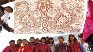 An art teacher, front left, shows pupils' paper-cutting samples depicting dragons at a primary school in Zouping county, China