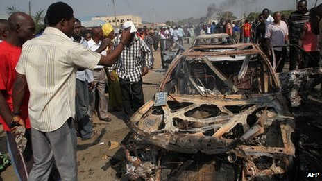 People gather around burnt cars near St Theresa Catholic Church after a bomb blast in the Madala Zuba district of Nigeria's capital Abuja on 25 December 2011. Two explosions near churches during Christmas Day services in Nigeria, including one outside the country's capital, killed at least 28 people amid spiralling violence blamed on an Islamist group.