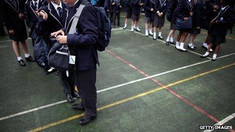 Pupils wait in a playground