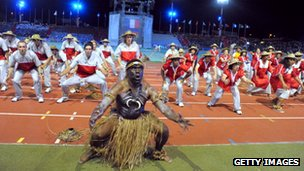 A dancer in traditional costume and athletes of the Caledonian delegation perform a haka during the Opening Ceremony for the 14th Pacific Games in Noumea, New-Caledonia