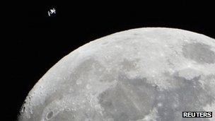 International Space Station is seen as a small object in the upper left of this image of the moon from Houston, Texas, 4 January 2012