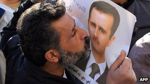 A government supporter kisses a picture of President Assad in Damascus