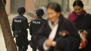 Armed Chinese police (L) patrol on a street as Ethnic Tibetans walk past in Chengdu in southwest China's Sichuan province on January 27, 2012.