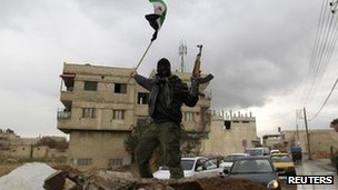 A soldier who has defected to the Free Syrian Army waves a Syrian independence flag in Saqba near Damascus