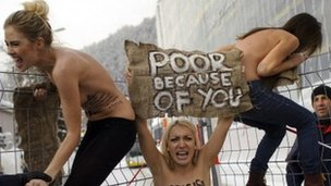 Topless female protesters holding a sign saying &quot;poor because of you&quot;