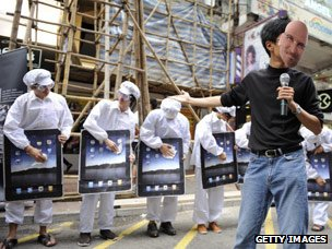 Protester in a Steve Jobs mask takes part in a demonstration against factory conditions in China