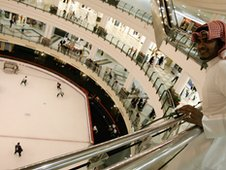 A man from Qatar watches ice hockey in the City Centre Mall in the West Bay section of Doha