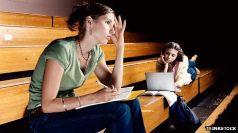 Students in lecture hall, one with exercise book, the other with a laptop