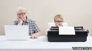 Man on laptop, boy on typewriter