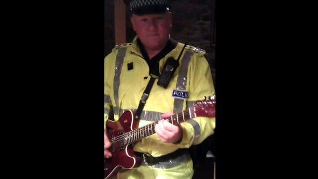 A Northern Constabulary officer playing guitar