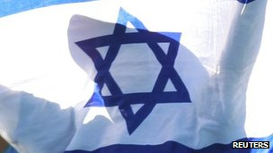 A child holds an Israeli flag during a tennis match