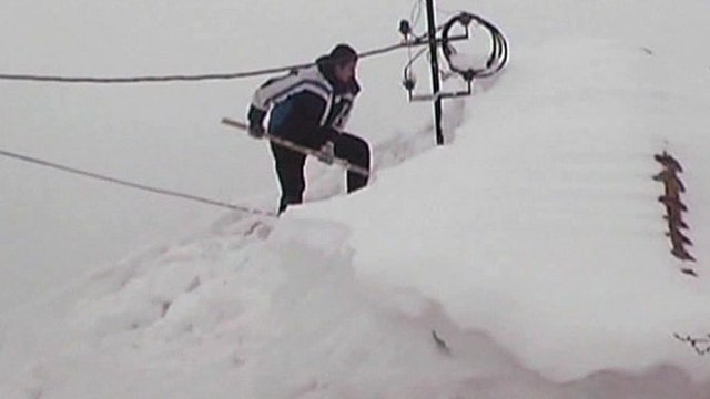 Man digging snow from roof