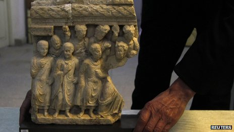 An Afghan specialist displays the ancient pre-Islamic sculpture returned by Germany
