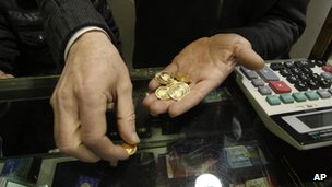 An Iranian goldsmith counts his gold coins at a gold market in Tehran (26 January 2012)