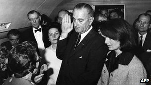 Jacqueline Kennedy (R) watches as US Vice-President Lyndon Johnson (C) is administered the oath of office