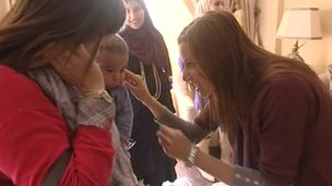 An Egyptian lady greets a mother and child