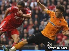 Matt Doherty slides in on Liverpool's Andy Carroll