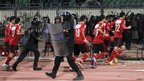 Riot police guard al-Ahly players as they leave the pitch