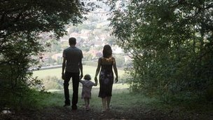 A mother, father and child walking in the countryside