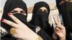 Kuwaiti's give a victory sign as they stand in front of a polling station in Jahra.