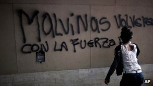A woman in Buenos Aires finishes graffiti which reads: We will get Malvinas back with the strength of...""