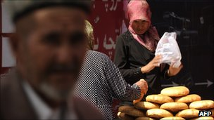 A Muslim ethnic Uighur woman sells bread on a street in Urumqi, capital of China&#039;s Xinjiang region.