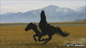 A herder rides his horse at a field under the Tianshan Mountain