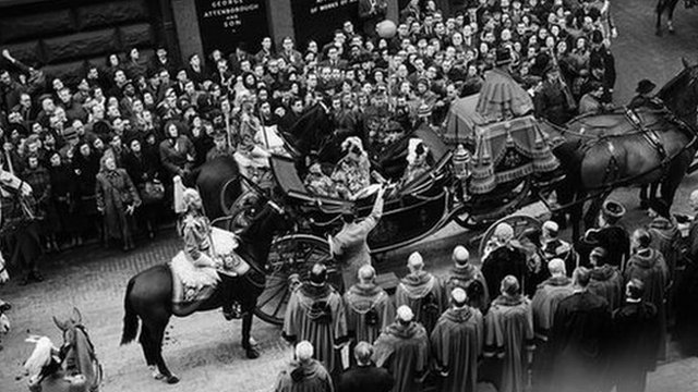 Crowds watch a parade to celebrate the proclamation of Queen Elizabeth II's accession to the throne, Feb 1952
