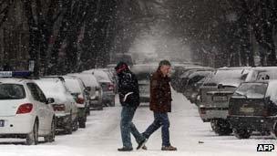 Two men cross a snowy street in Nis, Serbia on 2 February, 2012