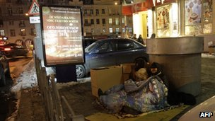 Homeless people sit by an air vent in Kiev, Ukraine (31 Jan 2012)