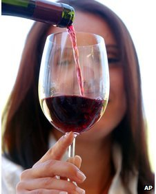 Woman being poured a glass of wine
