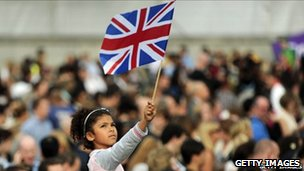 Young girl in crowd waving union jack flag