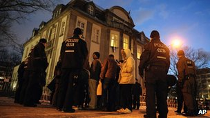 German police surround protesters outside the Syrian embassy.