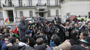 A protester holds a megaphone and a toy gun amongst crowds of Syrians protesting outside the Syrian Embassy in London