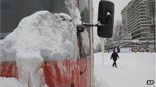 A Bosnian man walks near a frozen tram in the Bosnian capital of Sarajevo, on February 4