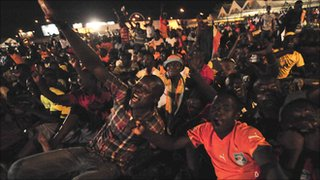Ivorian fans celebrate an Elephants goal as they watch on a big screen in Abidjan