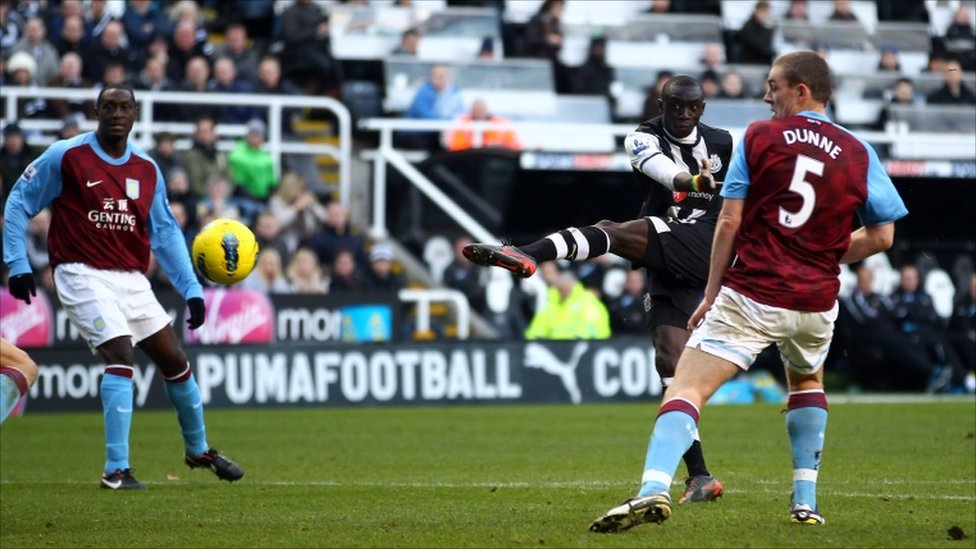 Papiss Demba Cisse scores for Newcastle, while Aston Villa's Emile Heskey and Richard Dunne look on