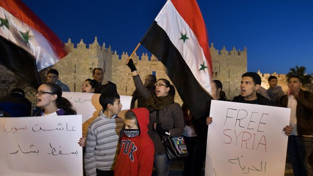 Demonstrators wave Syrian flags