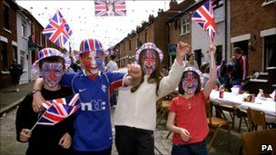 Children wave Union Jacks at street party