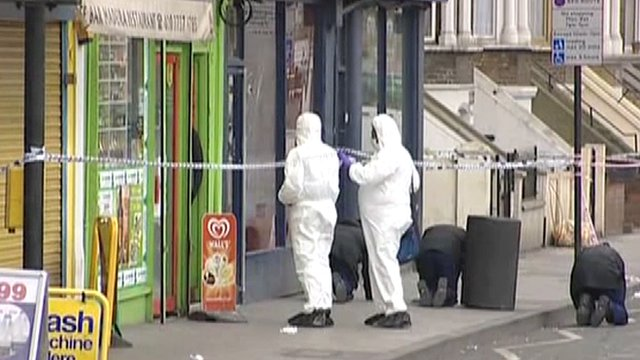Forensic officers gather evidence outside the shop where the shooting happened