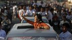 Burma&#039;s pro-democracy leader Aung San Suu Kyi waves at crowds 