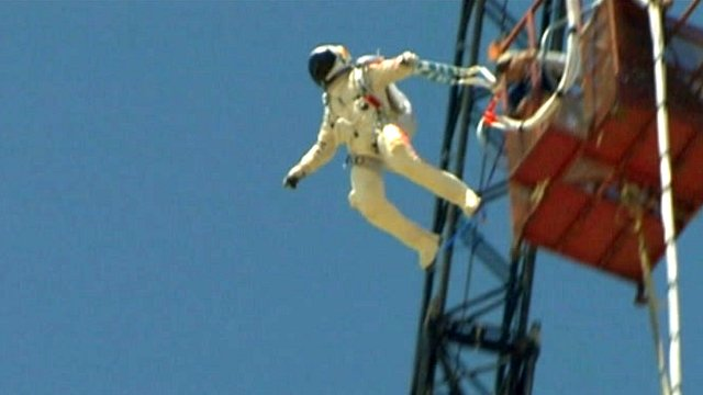 Man in space suit does bungee jump