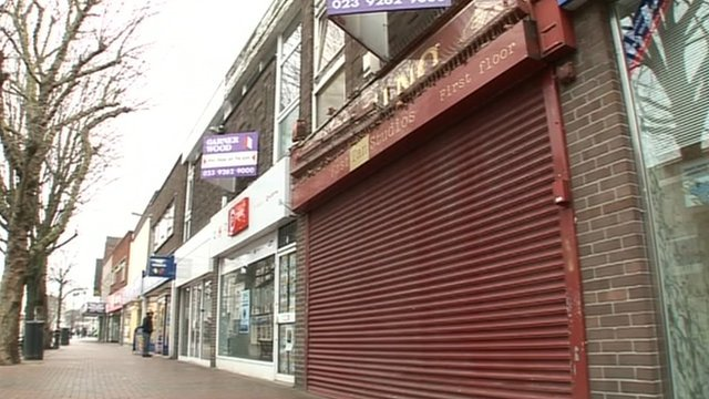 Row of high street shops, one with the shutter drawn down.